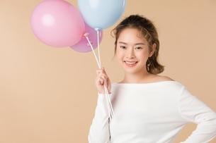 カラフルな風船を持っている可愛い女性の写真素材 [FYI04682936]