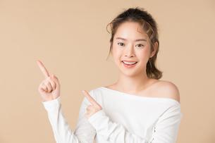 横に指差しをしている可愛い女性の写真素材 [FYI04682937]