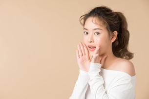 両手を口に当てて何かをアナウンスするポーズをする可愛い女性の写真素材 [FYI04682939]