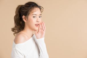 手を口に当てるポーズをしている若い女性モデルの写真素材 [FYI04682940]