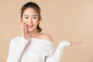 手ですすめるのジェスチャーをしている若い女性の写真素材 [FYI04682941]