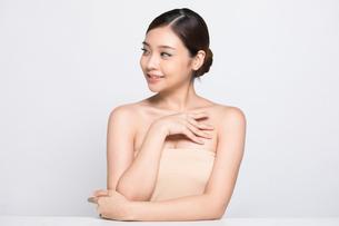 白バックの前で座るビューティーモデルの若い女性の写真素材 [FYI04683334]