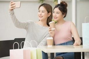 友達同士の若い女性二人がカフェでセルフィを撮りながらティータイムを楽しんでいるの写真素材 [FYI04683409]