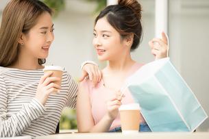 友達同士の若い女性二人がカフェでティータイムを楽しんでいるの写真素材 [FYI04683410]