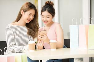 友達同士の若い女性二人がカフェでティータイムを楽しんでいるの写真素材 [FYI04683412]