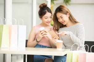 友達同士の若い女性二人がカフェでティータイムを楽しんでいるの写真素材 [FYI04683413]