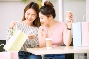 友達同士の若い女性二人がカフェでティータイムを楽しんでいるの写真素材 [FYI04683417]