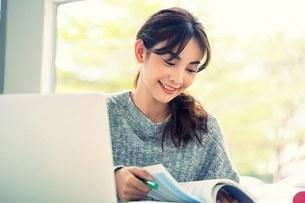 ノートパソコンと教科書で勉強している美人女子大生の写真素材 [FYI04683433]