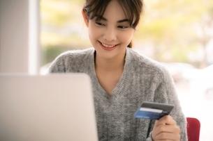 クレジットカードでオンラインショッピングをしている若い女性の写真素材 [FYI04683434]