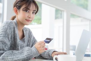 クレジットカードでオンラインショッピングをしている若い女性の写真素材 [FYI04683436]