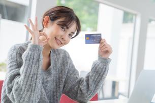 クレジットカードを持ちながら手でOKサインをする綺麗な若い女性の写真素材 [FYI04683437]