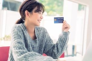 クレジットカードをすすめる綺麗な若い女性の写真素材 [FYI04683438]