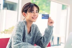 クレジットカードをすすめる綺麗な若い女性の写真素材 [FYI04683439]
