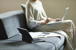 ソファに座った女性とタブレットPCの写真素材 [FYI04683739]