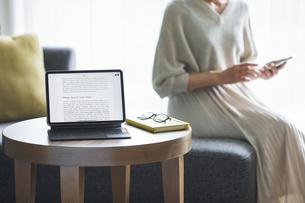 ソファに座った女性とタブレットPCの写真素材 [FYI04683817]