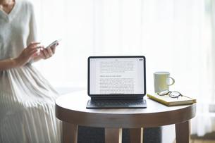 タブレットPCとソファと座る女性の写真素材 [FYI04683858]