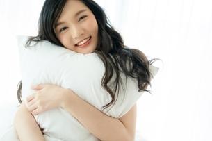 枕を抱きながら笑顔を浮かべる若い女性の写真素材 [FYI04683867]