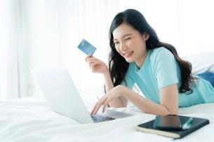 クレジットカードでオンラインショッピングを楽しんでいる若い女性の写真素材 [FYI04683874]