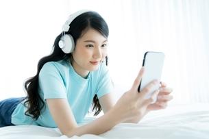ワイヤレスヘッドフォンで音楽を聴きながら携帯電話で遊んでいる若い女性の写真素材 [FYI04683881]