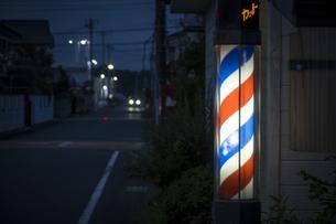 街灯の明かりと床屋の電照看板の写真素材 [FYI04684121]