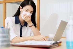 辛そうな表情で仕事をしているマスク姿の若い女性社員の写真素材 [FYI04684458]