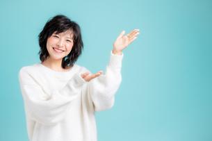 手でどうぞのジェスチャーをしている若い女性の写真素材 [FYI04684718]