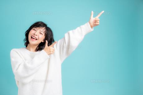 手をあげて指差しをしている若い女性の写真素材 [FYI04684720]