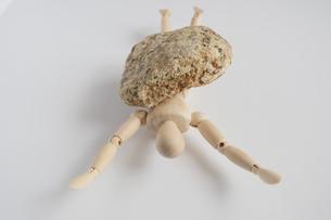 石に押しつぶされるデッサン人形の写真素材 [FYI04684951]