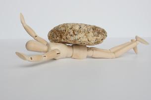 石に押しつぶされるデッサン人形の写真素材 [FYI04684953]