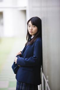 壁にもたれ掛かる女子高生の写真素材 [FYI04685301]