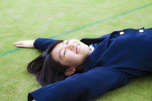グラウンドの芝生に寝転がる女子高生の写真素材 [FYI04685326]