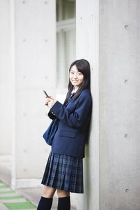 スマートフォンをいじる女子高生の写真素材 [FYI04685334]