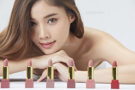 たくさんのリップスティックを前に並べてその後ろから笑顔を出す美人女性の写真素材 [FYI04685629]