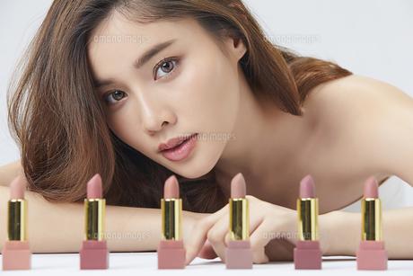 たくさんのリップスティックを前に並べてその後ろから顔を出す美人女性の写真素材 [FYI04685630]