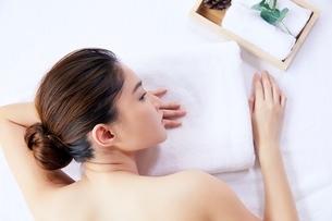 スパマッサージを受ける前に横になってリラックスしている美人女性の写真素材 [FYI04685632]