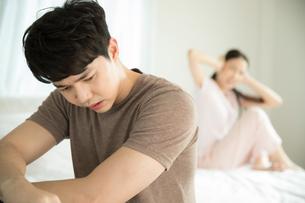 夫婦喧嘩中で手で耳を塞いでしまう女性と落ち込む男性の写真素材 [FYI04685654]