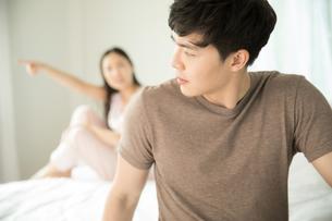 ベッドルームでケンカしている若い夫婦カップルの写真素材 [FYI04685655]