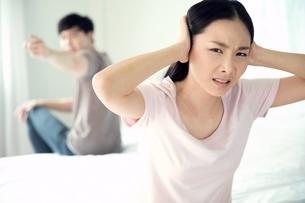 夫婦喧嘩中で旦那の声を聞き入れず手で耳を塞いでしまう女性の写真素材 [FYI04685656]