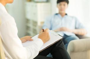 精神科で男性患者にカウンセリングをしている医師の写真素材 [FYI04685660]
