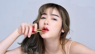 口紅を塗るセクシーな女性のポートレートの写真素材 [FYI04685913]