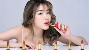 口紅を塗るセクシーな女性のポートレートの写真素材 [FYI04685914]