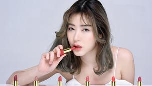 口紅を塗るセクシーな女性のポートレートの写真素材 [FYI04685916]