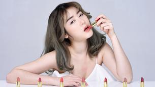 口紅を塗るセクシーな女性のポートレートの写真素材 [FYI04685917]