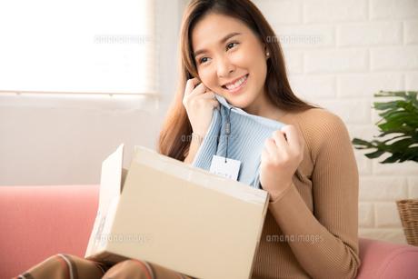 オンラインショッピングで買った商品が良かったと喜ぶ若い女性の写真素材 [FYI04685918]