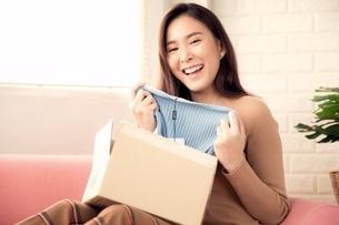 オンラインショッピングで買った商品が良かったと喜ぶ若い女性の写真素材 [FYI04685922]