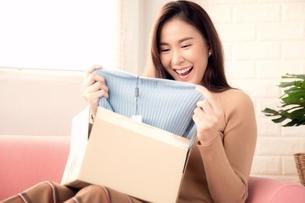 オンラインショッピングで買った商品が良かったと喜ぶ若い女性の写真素材 [FYI04685923]