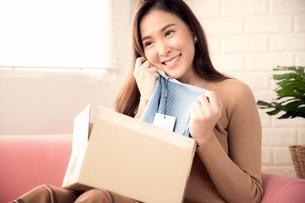 オンラインショッピングで買った商品が良かったと喜ぶ若い女性の写真素材 [FYI04685924]