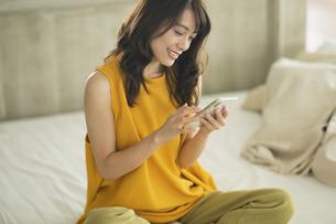ベッドに座りスマホを操作する女性の写真素材 [FYI04685925]