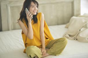 ベッドに座りスマホで通話する女性の写真素材 [FYI04685926]