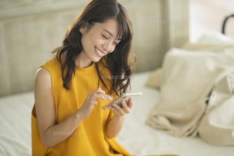 ベッドに座りスマホを操作する女性の写真素材 [FYI04685928]